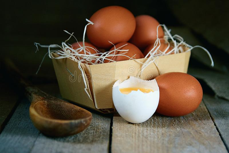Много яя деревни лежат в плетеной корзине в курятнике на деревянном поле стоковые изображения rf