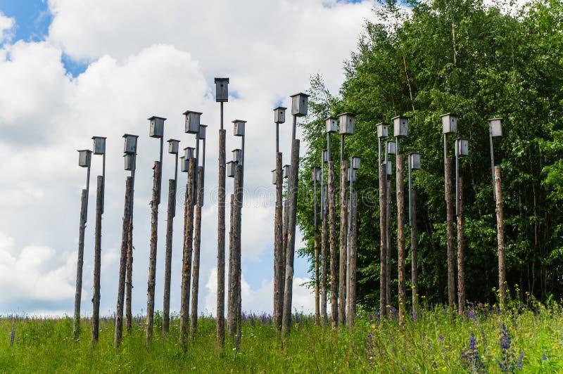 Много birdhouses на поляках в луге стоковое фото