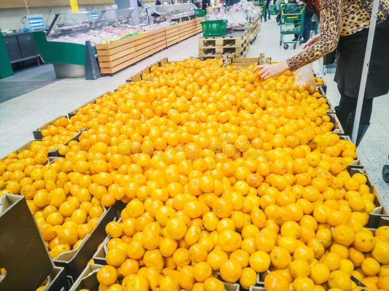 Много tangerines ходят по магазинам коробки и женщина стоковые изображения