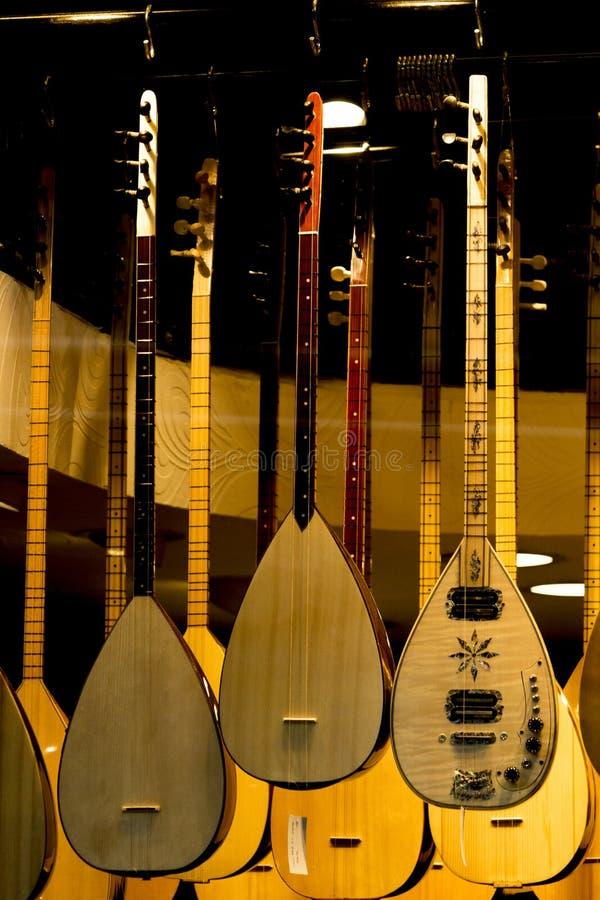 Множественное saz, турецкая длинная лютня шеи разных видов вися от потолка музыкального магазина стоковые фото