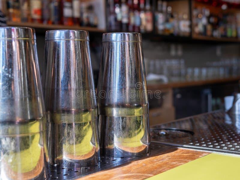 Множественные стальные шейкеры напитка сидя на countertop бара готовом для того чтобы сделать коктейли стоковое изображение rf