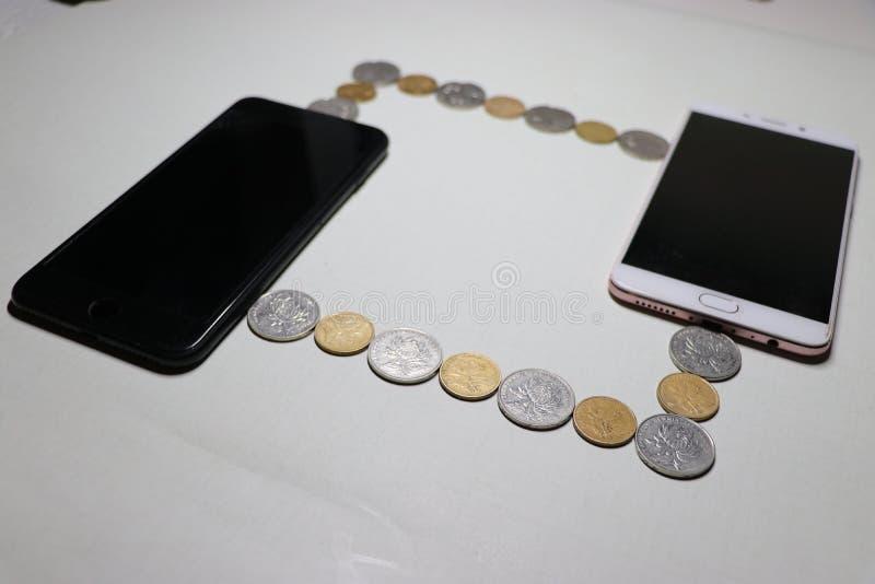 2 мобильного телефона соединены проводом составленного монеток стоковые фотографии rf