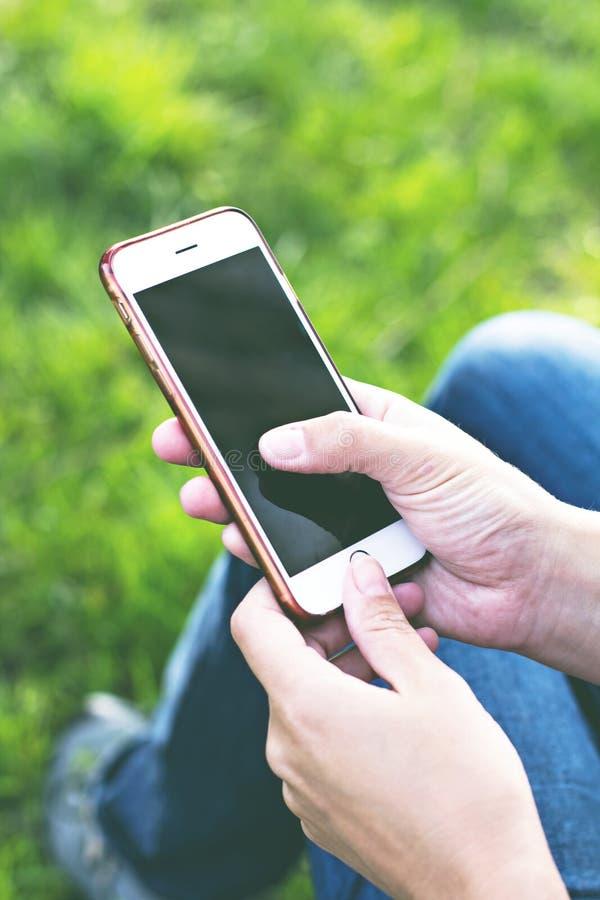 Мобильный телефон в руке женщины в deckchair на фоне реки Телефон, Deckchair, зеленая трава, река Время t стоковая фотография rf