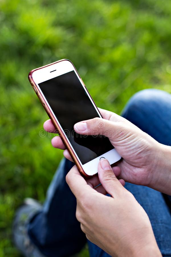 Мобильный телефон в руке женщины в deckchair на фоне реки Телефон, Deckchair, зеленая трава, река Время t стоковое изображение