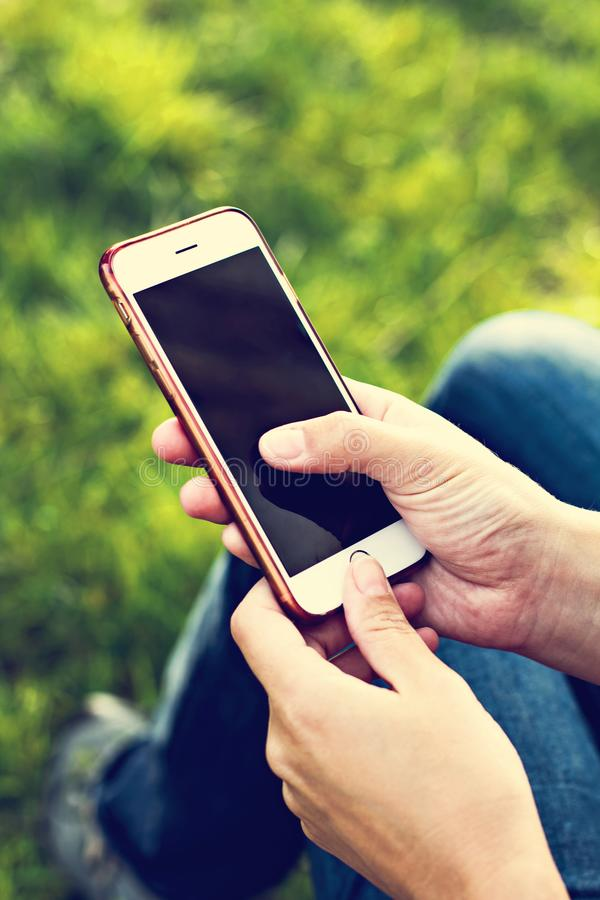 Мобильный телефон в руке женщины в deckchair на фоне реки Телефон, Deckchair, зеленая трава, река Время t стоковые фотографии rf