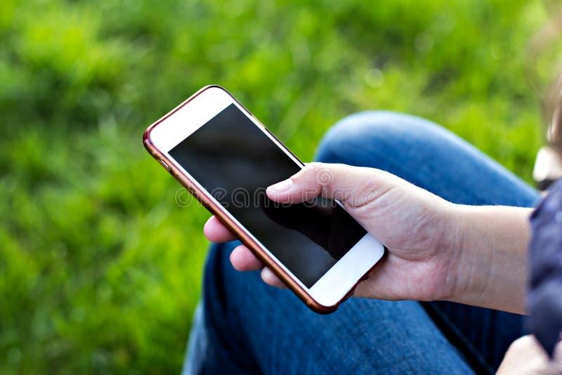 Мобильный телефон в руке женщины в deckchair на фоне реки Телефон, Deckchair, зеленая трава, река Время t стоковые фото