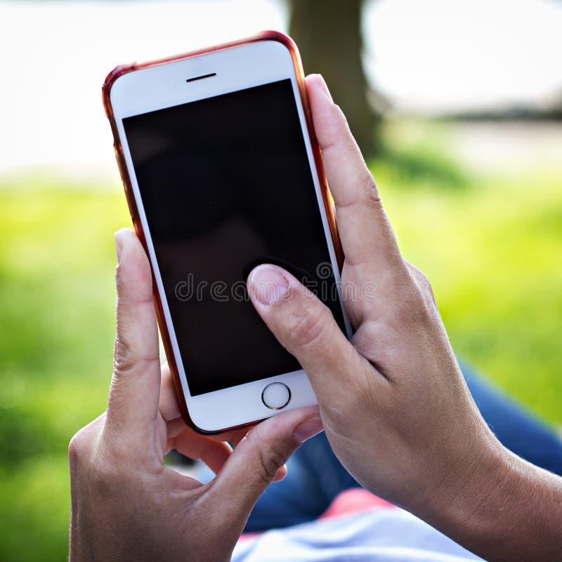 Мобильный телефон в руке женщины в deckchair на фоне реки Телефон, Deckchair, зеленая трава, река Время t стоковые изображения rf