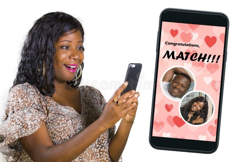 Мобильный телефон и молодая красивая и счастливая черная афро американская женщина используя онлайн датируя возбужденное приложен стоковое изображение