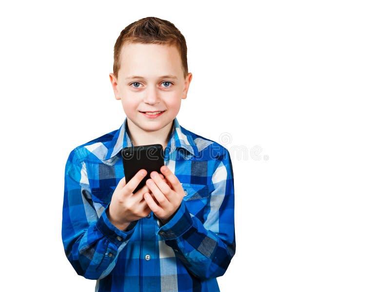Мобильный телефон и улыбки удерживания мальчика, изолированные на белой предпосылке стоковое фото rf