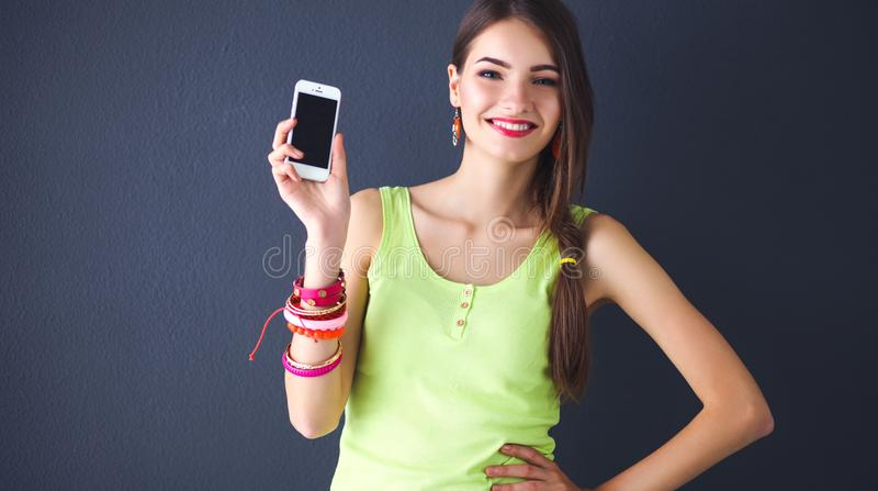 Мобильный телефон красивой молодой женщины holdiing, на сером цвете стоковое фото
