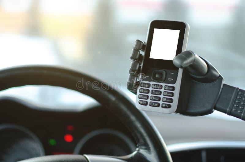 Мобильный телефон с пустым экраном в робототехнической руке на автомобиле стоковая фотография rf