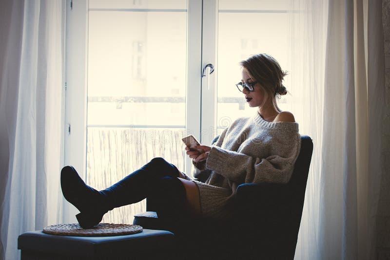 Мобильный телефон удерживания девушки и сидеть в кресле стоковое изображение rf