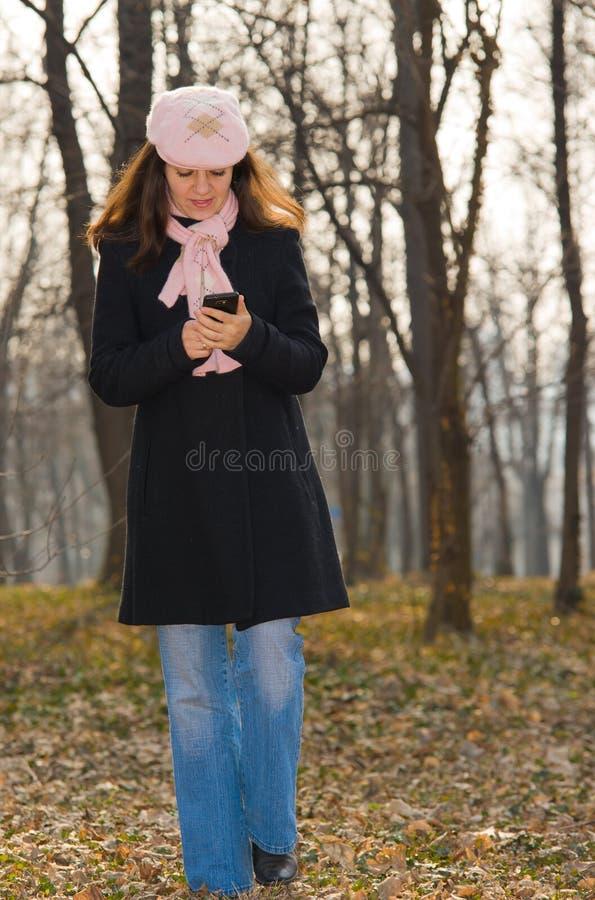 мобильный телефон outdoors используя гуляя детенышей женщины стоковые фотографии rf