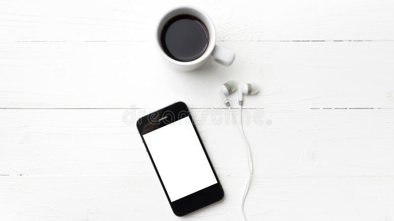 Мобильный телефон и кофейная чашка стоковые фото