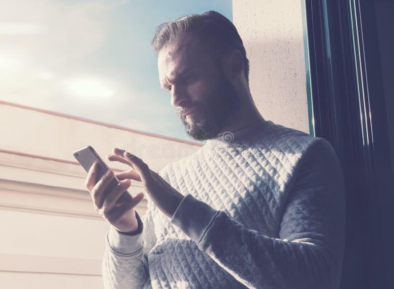 Мобильный телефон касающего экрана человека портрета бородатый Человек используя современный smartphone, солнечную предпосылку не стоковое фото rf
