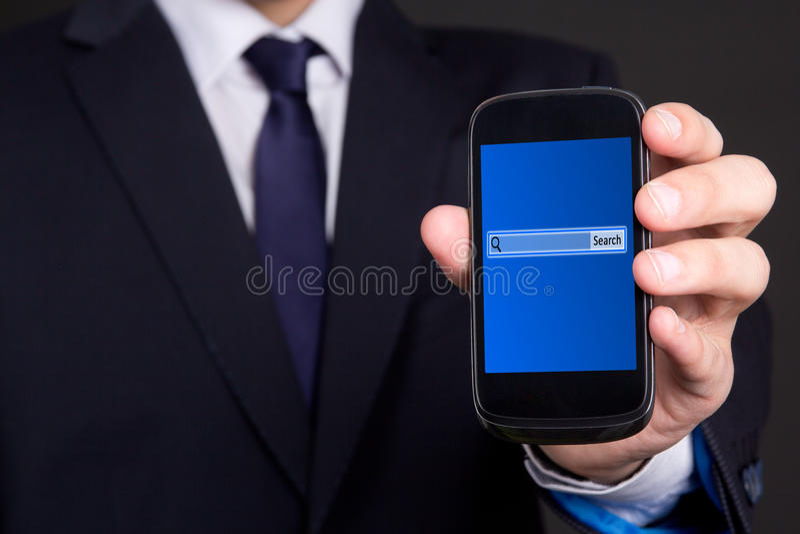 Мобильный телефон с баром поиска на экране в руке бизнесмена стоковые изображения