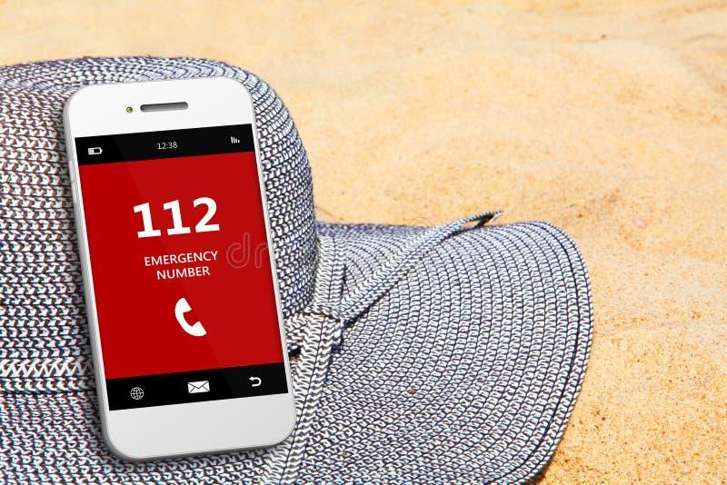 Мобильный телефон с номером службы экстренной помощи 112 на пляже стоковая фотография