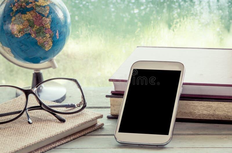 Мобильный телефон, умный телефон, телефон с книгой, глобус и eyeglasses стоковые изображения rf