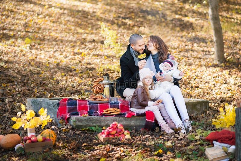 Мода осени для детей и целой семьи Мама, папа и 2 дет на пикнике в осени с яблоками, тыквами Семья я стоковое фото rf