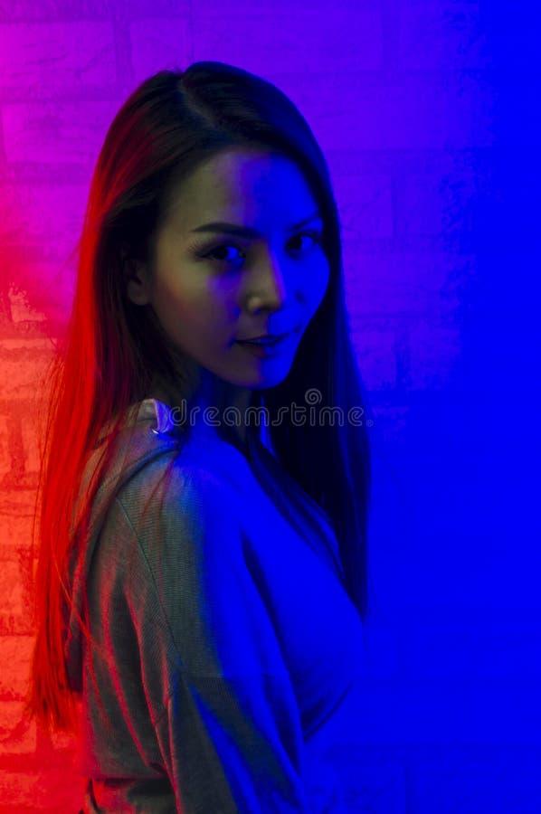 Мода портрета азиатской женщины в неон-фиолетовом и красном свете который светит в темноте с красотой и сексуальный, обольститель стоковая фотография rf