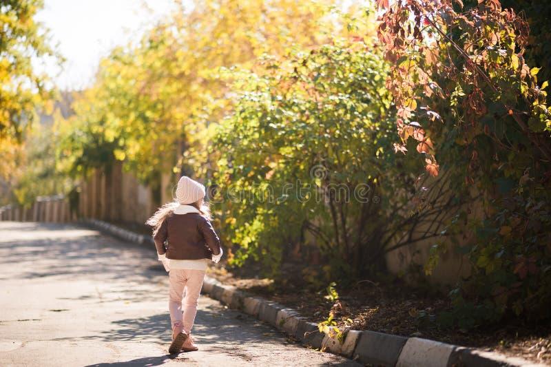 Мода ` s детей осени Маленькая девочка танцует, скачет и радуется осенью против предпосылки желтой и красной листвы дальше стоковая фотография rf