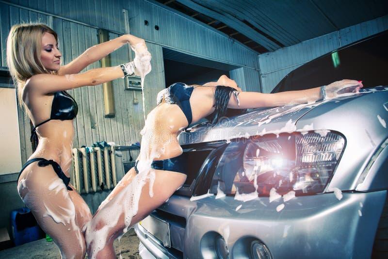 Модели на мытье автомобиля в гараже. стоковые изображения