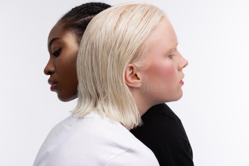 Модели с различным цветом кожи и волос обнимая пока представляющ стоковая фотография rf