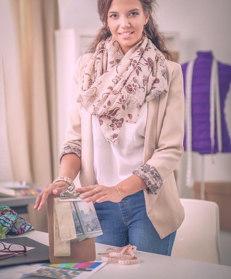 Модельер молодой женщины работая на студии стоковые фото