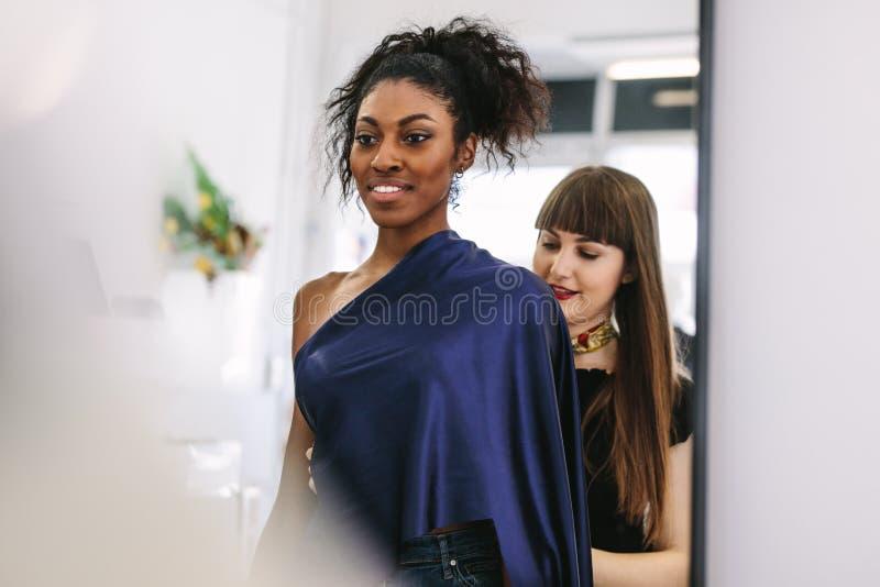 Модельер работая на дизайнах в ее студии дизайна моды стоковая фотография