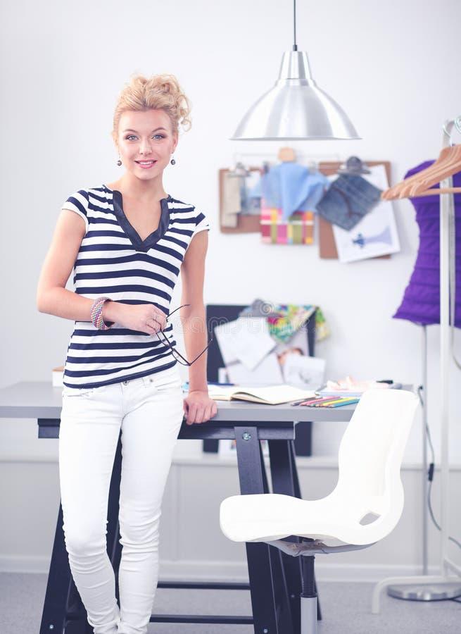 Модельер работая на ее дизайнах в студии стоковые фотографии rf