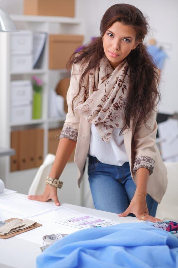 Модельер работая на ее дизайнах в студии стоковое фото