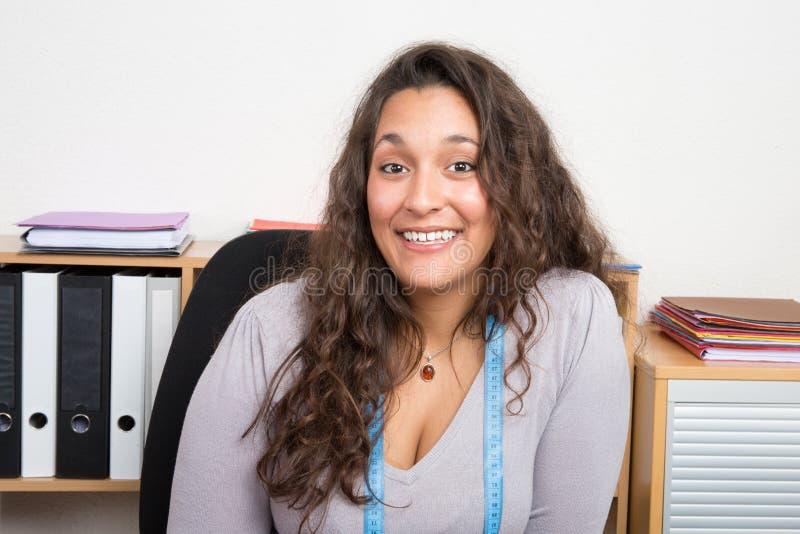 Модельер сидя на рабочем месте работая в ее студии стоковые фото