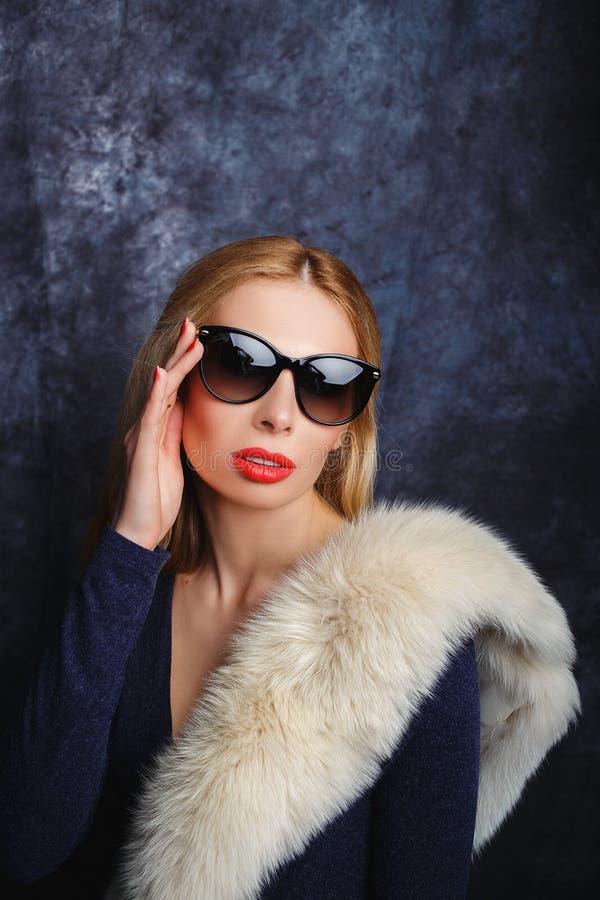 Модельная девушка в мехах и стеклах стоковые изображения