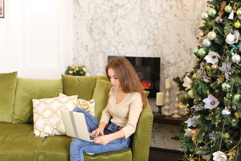 Модельная девушка используя компьтер-книжку для того чтобы ходить по магазинам на Новый Год стоковые фото