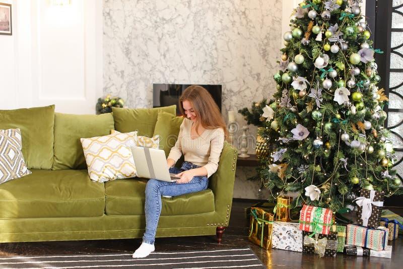 Модельная девушка используя компьтер-книжку для того чтобы ходить по магазинам на Новый Год стоковая фотография