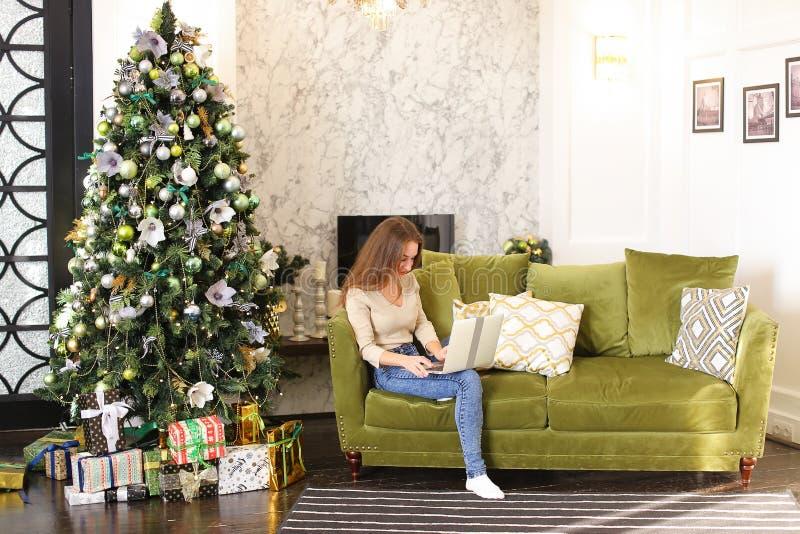Модельная девушка используя компьтер-книжку для того чтобы ходить по магазинам на Новый Год стоковое изображение