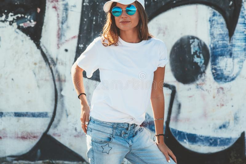 Модельная нося простые футболка и солнечные очки представляя над улицей wal стоковые фото