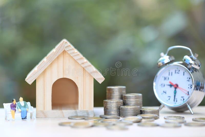 Модельный дом с миниатюрным положением пар на монетках деньгах и бутылка стекла с часами alrm на естественной зеленой предпосылке стоковое изображение rf
