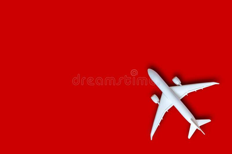 Модельный самолет, самолет на предпосылке красного цвета с космосом экземпляра, плоским положенным дизайном с белым самолетом, ко стоковое изображение rf