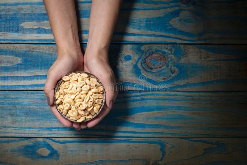 Модель брюнета держа керамический бак с зажаренными в духовке арахисами на голубой деревянной предпосылке стоковые изображения rf