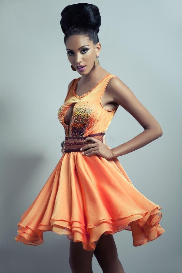 Модель в померанце flared платье стоковая фотография rf