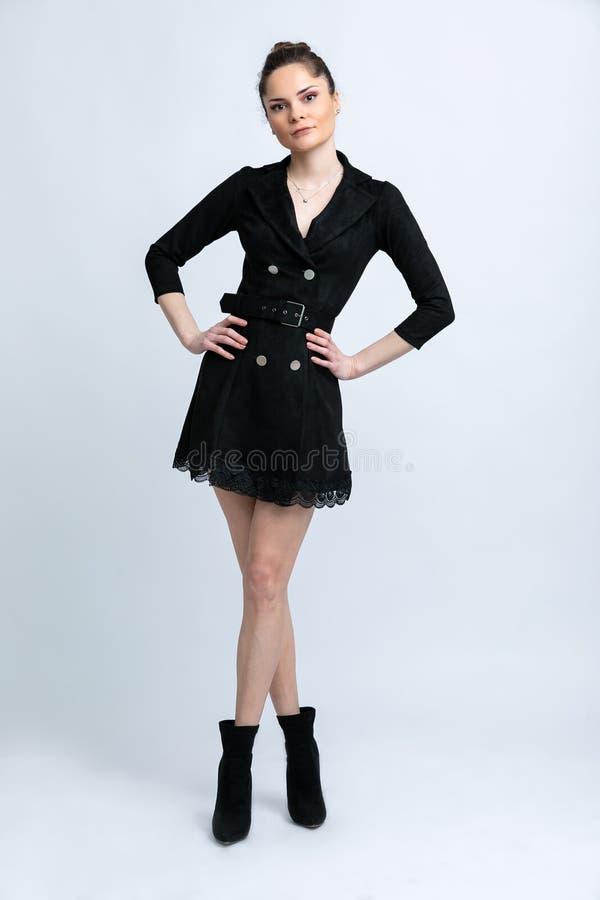Модель в черном пальто с поясом в черных ботинках с серебряными цепями на шеи, на белой предпосылке стоковые изображения