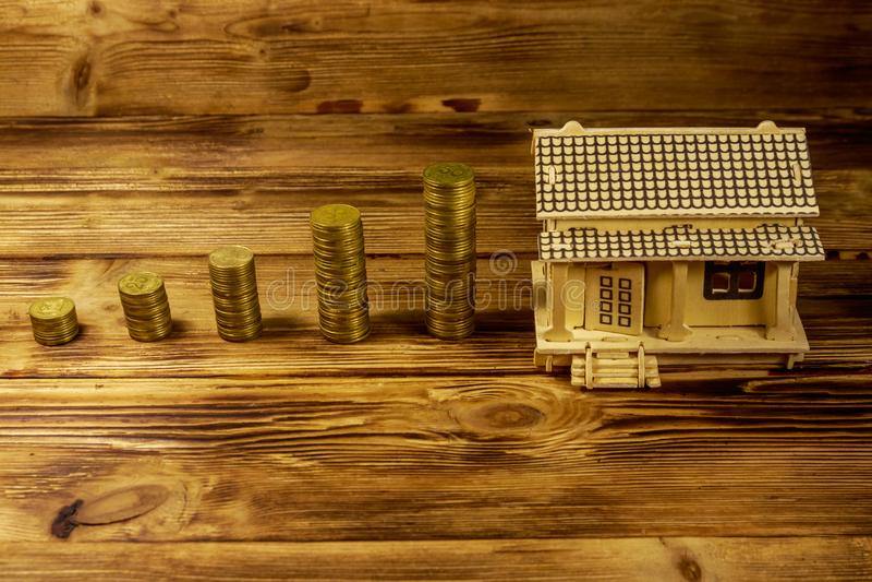 Модель дома и стога золотых монеток на деревянной предпосылке Вклад свойства, ипотечный кредит, ипотека дома, концепция недвижимо стоковые изображения rf