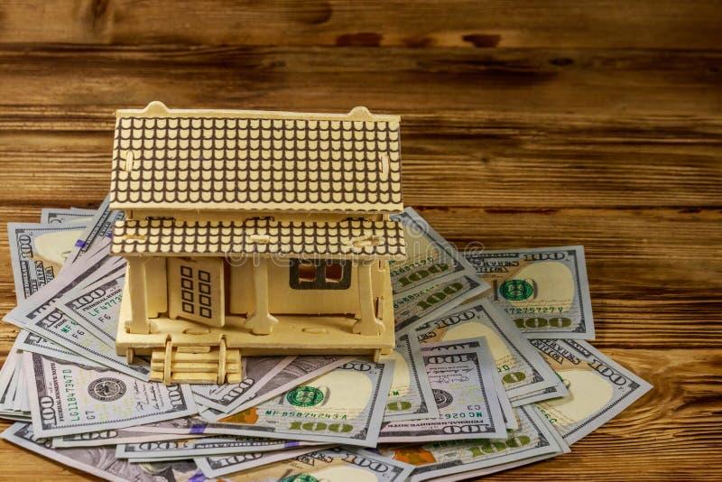 Модель дома и U S сто долларовых векселей на деревянном фоне Инвестиции в недвижимость, жилищный заем, ипотека на дом, недвижимос стоковая фотография rf