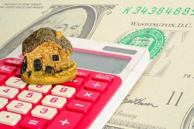 Модель дома на калькуляторе с предпосылкой доллара Займы недвижимости или сохранить деньги для покупки нового дома для стоковые фотографии rf