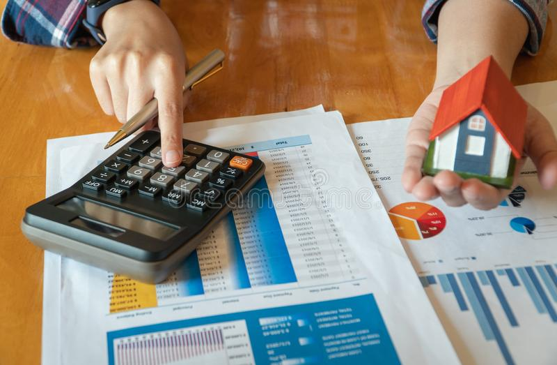 Модель дома удерживания женщины в руке и высчитывать финансовую диаграмму для вклада к покупая свойству стоковое фото