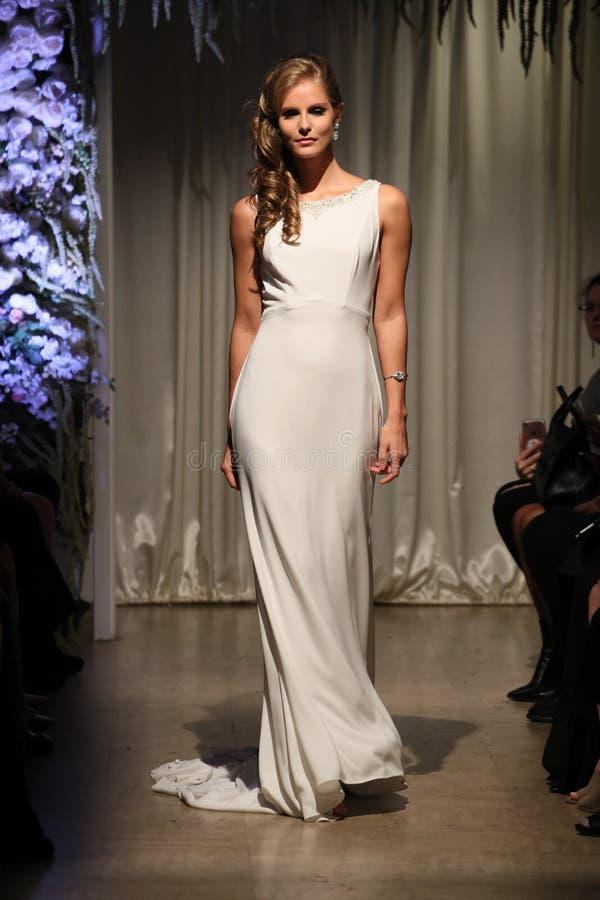 Модель идет взлётно-посадочная дорожка нося платья Мэттью Кристофера на неделе моды NY Bridal стоковое фото