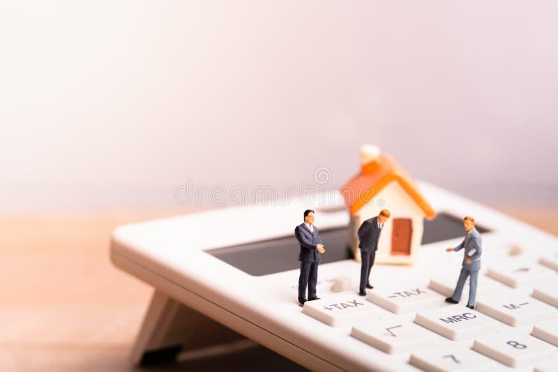Модель и businessmans дома на калькуляторе с налогом слова стоковая фотография rf