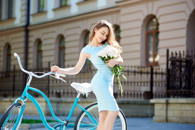Модель конца-вверх молодая представляя с пионами приближает к винтажному велосипеду стоковая фотография rf