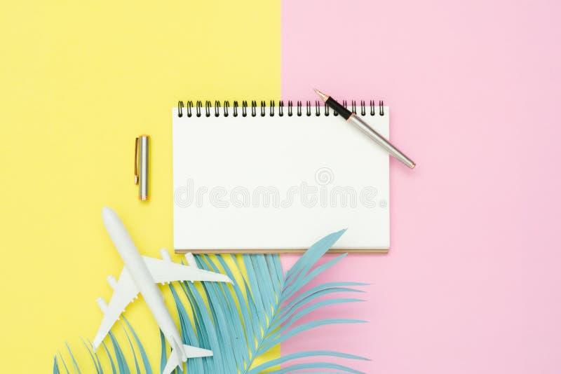 Модель-макет взгляд сверху тетради чистого листа бумаги, ручки, пастельных лист кокоса и самолета на розовом желтом экране пастел стоковое изображение